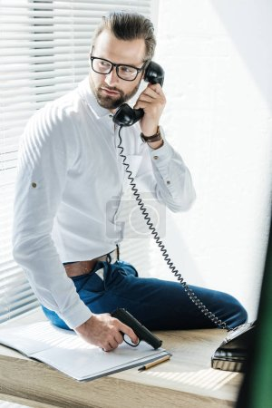 businessman holding gun while talking on rotary telephone in office