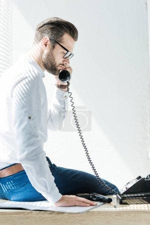 Foto de Barbudo hombre de negocios hablando por teléfono rotatorio mientras está sentado en la mesa con pistola - Imagen libre de derechos