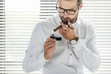 handsome businessman smoking cigar with lighter