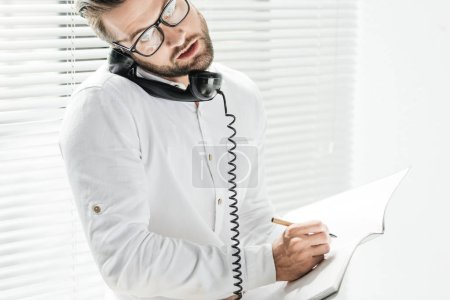 handsome businessman talking on rotary telephone while writing in notebook