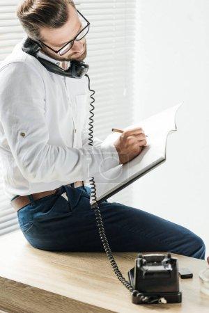 Foto de Empresario hablando por teléfono rotatorio al escribir en el cuaderno - Imagen libre de derechos