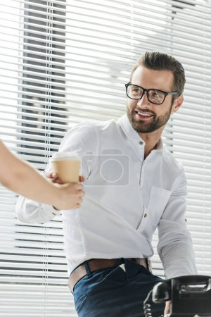 smiling businessman taking coffee to go from colleague