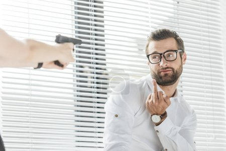 businessman showing middle finger to person with gun