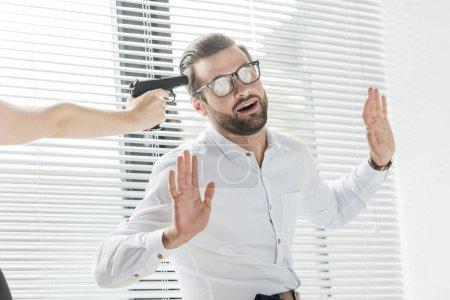 homme d'affaires, levant les bras tandis que quelqu'un qui tient l'arme à feu près de sa tête