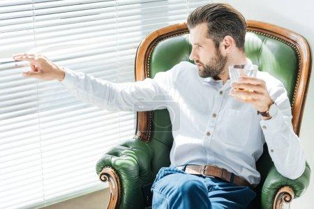 Photo pour Barbu élégant avec verre de whisky et assis dans le fauteuil vert et à la recherche dans la fenêtre - image libre de droit