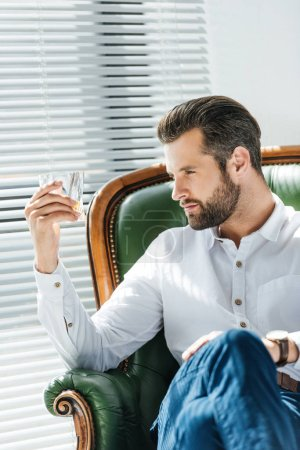 fashionable man looking at glass of whiskey and sitting in armchair