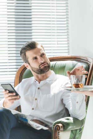 handsome stylish man using smartphone while taking whiskey glass from tray