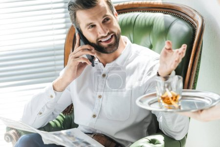 bearded man with newspaper talking on smartphone while taking whiskey glass from tray