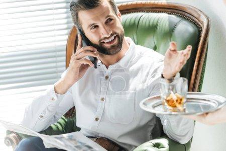 Photo pour Homme barbu avec journal parlant sur smartphone tout en prenant verre de whisky de plateau - image libre de droit