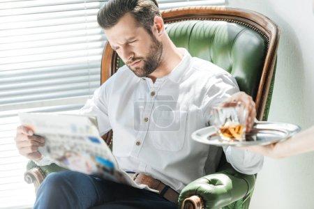 Photo pour Élégant homme sérieux lecture journal tout en prenant verre de whisky de plateau - image libre de droit