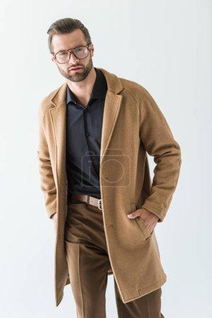 Photo pour Homme à la mode en lunettes et manteau brun, isolé sur blanc - image libre de droit