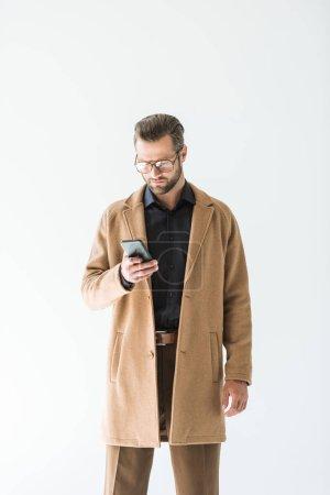 Photo pour Bel homme barbu en tenue d'automne à l'aide de smartphone, isolé sur blanc - image libre de droit