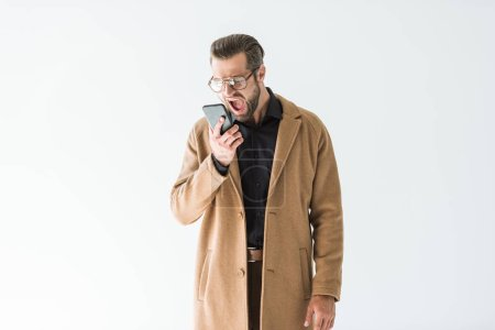 Photo for Angry man in autumn outfit yelling at smartphone, isolated on white - Royalty Free Image