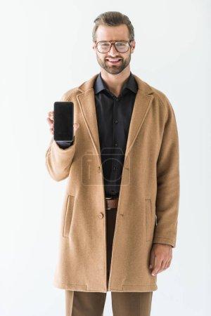 Barbu souriant homme présentant des smartphone avec un écran vide, isolé sur blanc