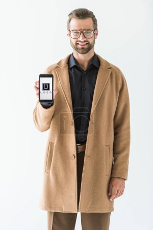 handsome smiling man presenting smartphone with uber appliance, isolated on white