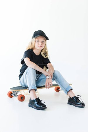 full length view of kid in black cap and t-shirt sitting on longboard and looking at camera isolated on white