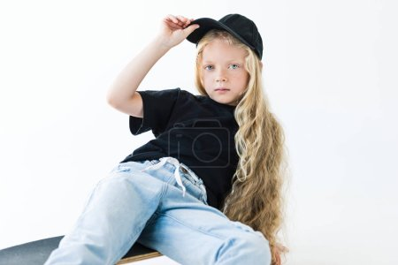 beautiful child with long curly hair adjusting cap and looking at camera while sitting on skateboard isolated on white