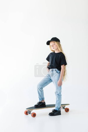 full length view of cute kid in black cap and t-shirt standing on skateboard isolated on white