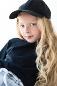 portrait of beautiful child with long curly hair wearing black t-shirt and cap, looking at camera isolated on white