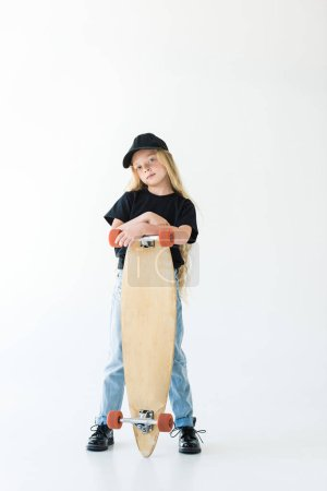full length view of beautiful child in black cap and t-shirt standing with skateboard and looking at camera isolated on white