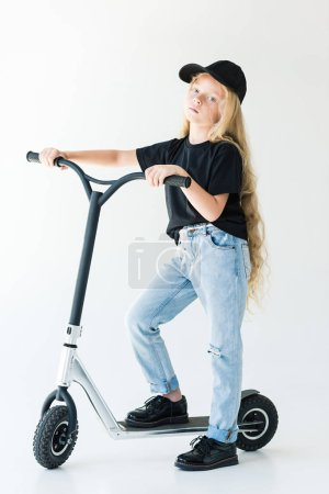 full length view of child in black t-shirt and cap riding scooter and looking at camera isolated on white