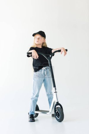 full length view of kid with long curly hair standing with scooter and looking away isolated on white