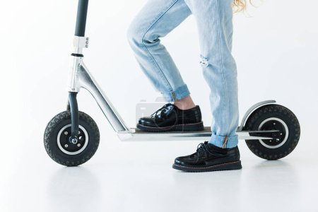 cropped shot of child in denim pants and black shoes riding scooter on white