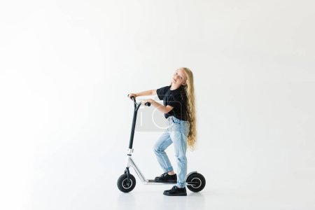 full length view of kid with long curly hair riding scooter and looking at camera isolated on white