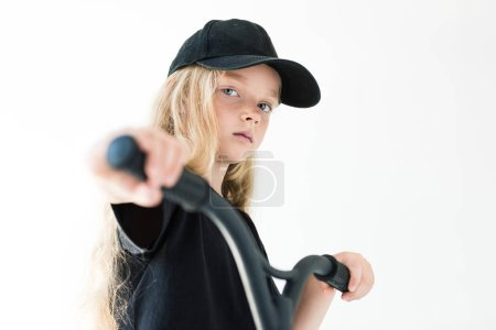 beautiful kid in black t-shirt and cap riding scooter and looking at camera isolated on white