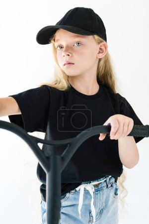 adorable child in black t-shirt and cap riding scooter and looking at camera isolated on white