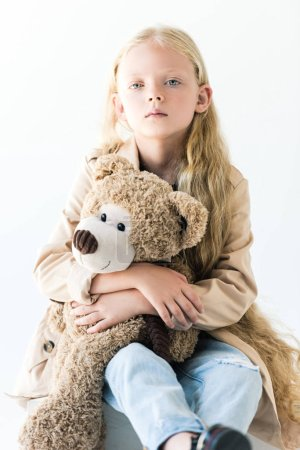 adorable child with long curly hair holding teddy bear and looking at camera isolated on white