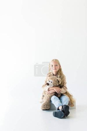 full length view of beautiful little child holding teddy bear and smiling at camera while sitting isolated on white
