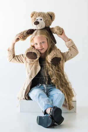full length view of beautiful stylish kid holding teddy bear and smiling at camera isolated on white