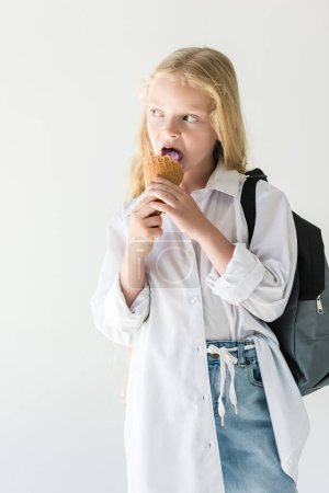 beautiful kid with backpack eating ice cream and looking away isolated on white