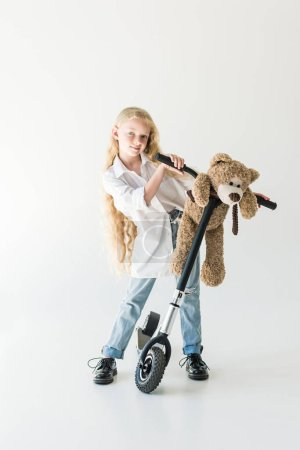 adorable child with long curly hair standing with scooter and teddy bear, smiling at camera on white