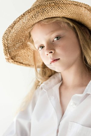 portrait of beautiful little kid in wicker hat looking at camera on white