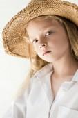 portrait of beautiful little kid in wicker hat looking at camera on white