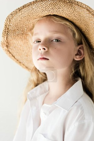 portrait of beautiful child in straw hat looking at camera on white