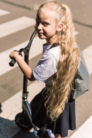 high angle view of beautiful little schoolgirl with long curly hair riding scooter and looking at camera