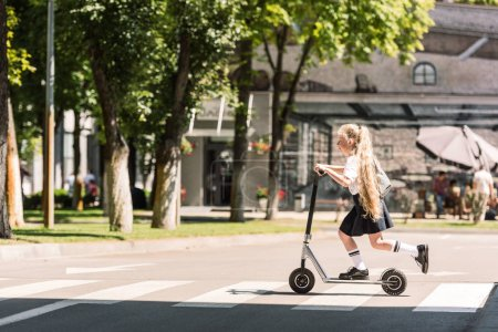 Photo for Side view of cute little schoolgirl with long curly hair riding scooter on street - Royalty Free Image