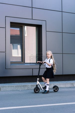 adorable little schoolgirl with long curly hair riding scooter and looking at camera on street