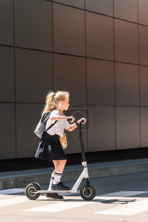 side view of adorable little schoolgirl with backpack riding scooter on street