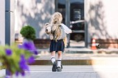 rear view of adorable schoolchild with backpack and teddy bear riding scooter on street