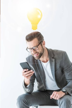 successful businessman using smartphone, isolated on white with idea light bulb