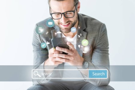 smiling SEO developer in gray suit using smartphone, isolated on white with website search bar and icons