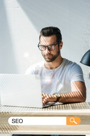 handsome developer working with laptop with SEO search bar