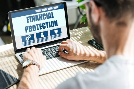 Photo for Back view of man using laptop with financial protection website - Royalty Free Image