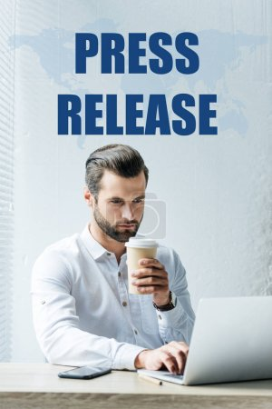 "concentrated businessman holding coffee to go while working with laptop, with ""press release"" lettering on world map"