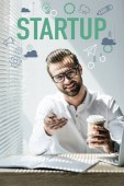 successful businessman sitting at workplace with startup icons