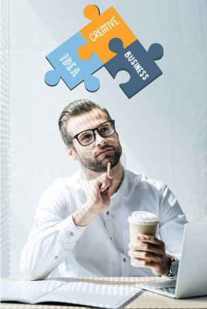 thoughtful businessman sitting at workplace with idea, creative, business words puzzle